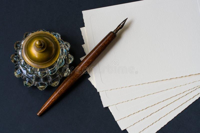 Vulpen, inktpot, documenten op een geweven zwarte stock afbeelding