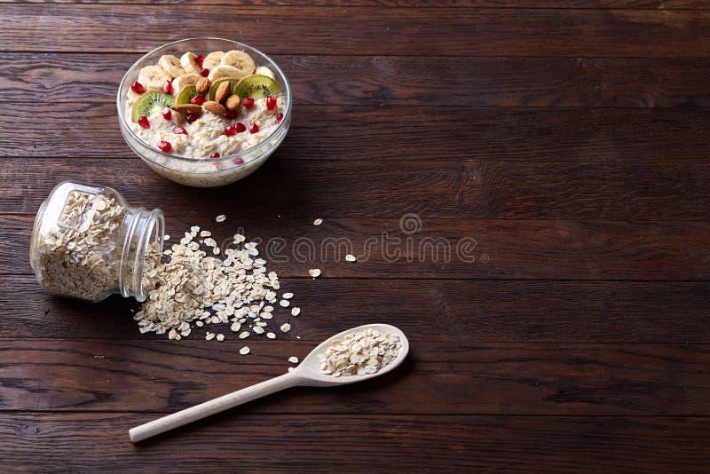 Vulten glass krus och sked med den rå havremjölet på tappningträbakgrund, närbild, selektiv fokus fotografering för bildbyråer