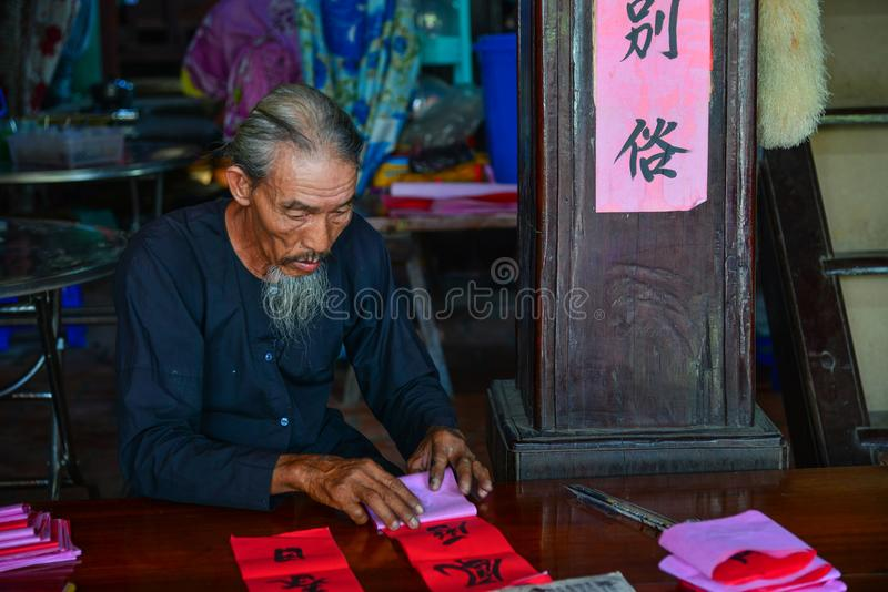 Writing chinese calligraphy on red paper royalty free stock photography