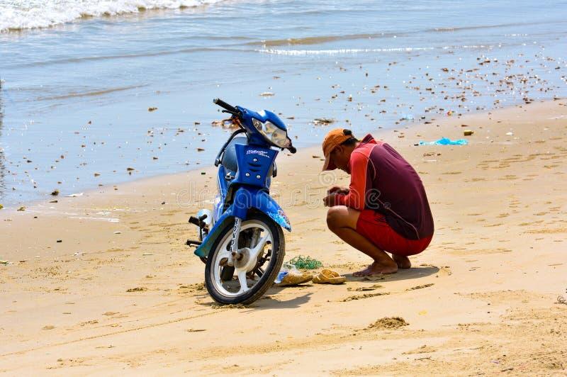 Vungtau, Vietnam - Januari 26, 2018: Een lokale mens herstelt een motorfiets op het strand stock foto