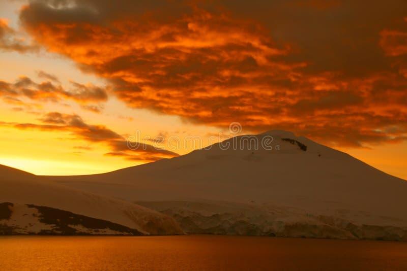 Vurige zonsondergang over ijzige berg stock afbeelding