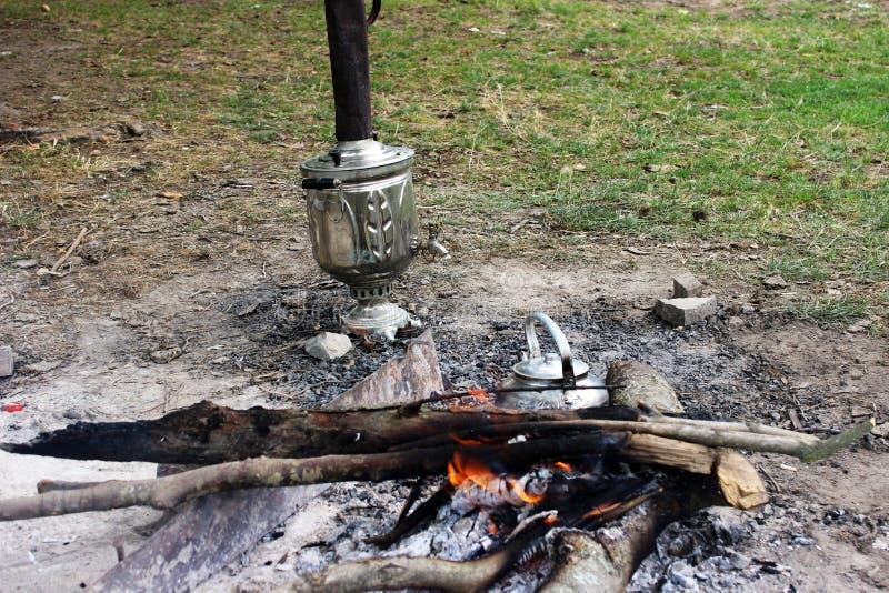 Vuur, de reisketel van het ijzermetaal, samovar en hete steenkolen stock afbeeldingen