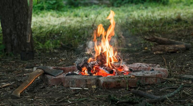 Vuur met dichtbij het branden firewoods daarin en oude bijl royalty-vrije stock foto