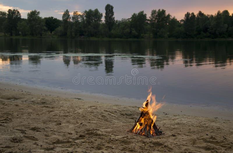 Vuur op de bank van de rivier bij zonsondergang stock afbeeldingen