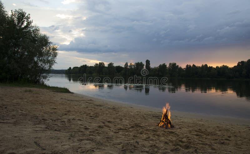 Vuur op de bank van de rivier bij zonsondergang stock foto's