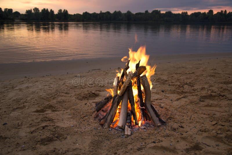 Vuur op de bank van de rivier bij zonsondergang royalty-vrije stock afbeelding