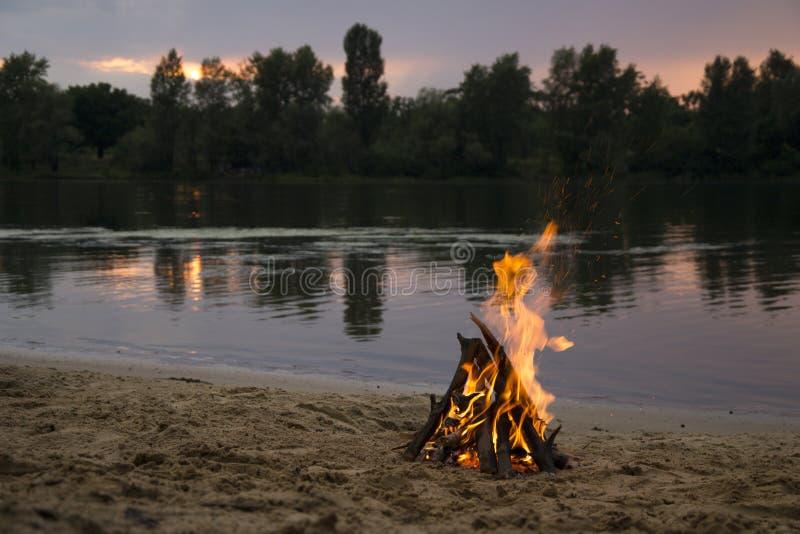 Vuur op de bank van de rivier bij zonsondergang royalty-vrije stock foto's