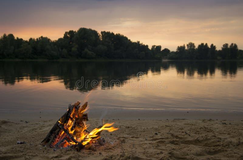 Vuur op de bank van de rivier bij zonsondergang royalty-vrije stock afbeeldingen
