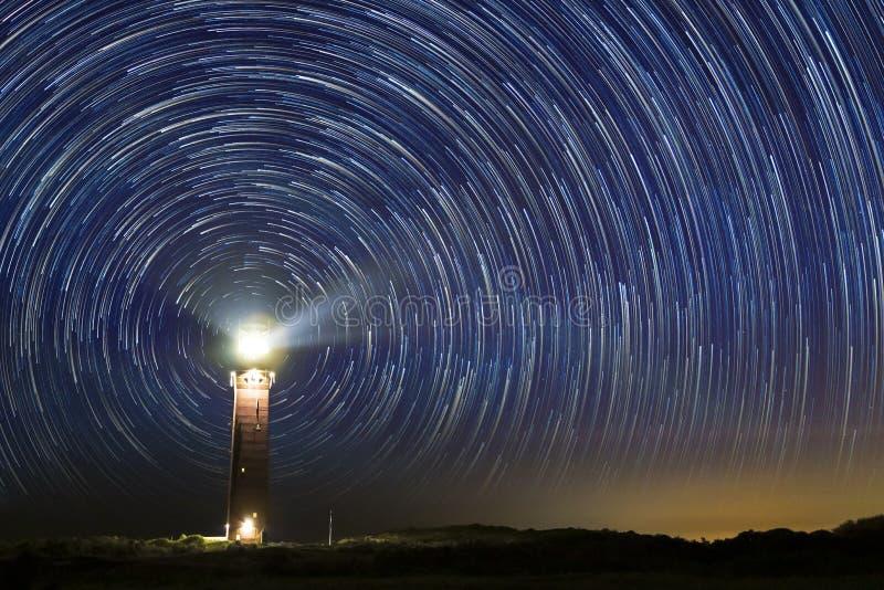 Vuurtoren bij nacht met sterslepen op het centrum stock afbeeldingen