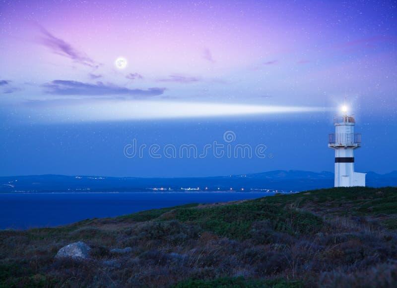 Vuurtoren die lichte straal over stormachtige wolken richt royalty-vrije stock afbeeldingen