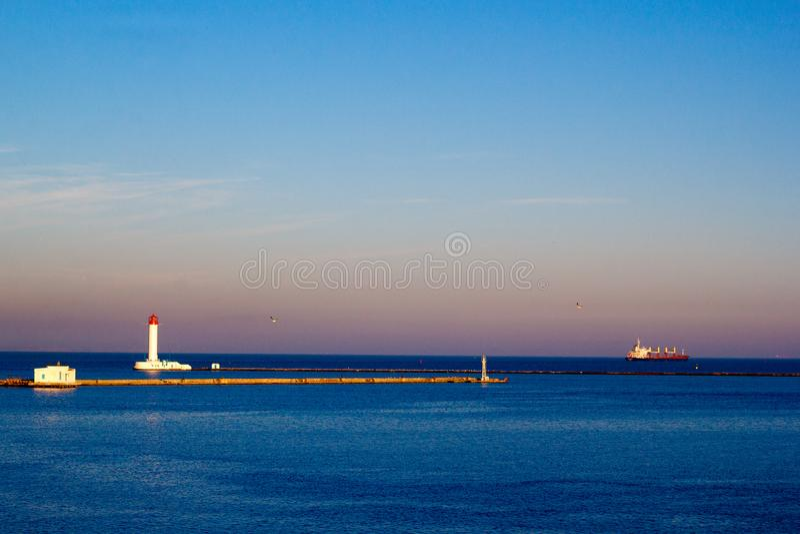 Vuurtoren en vrachtschip die een haven in de avond verlaten royalty-vrije stock fotografie