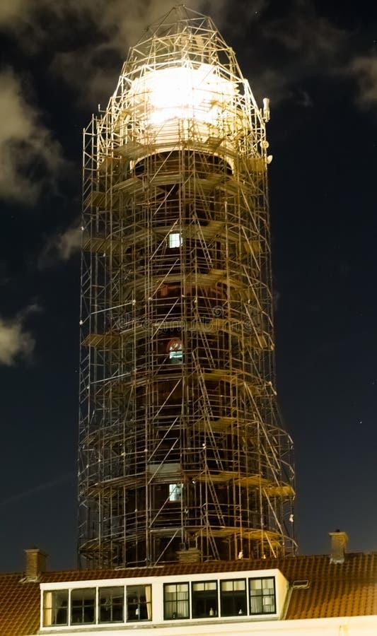 Vuurtoren in steiger voor bouw met het licht die bij nacht glanzen royalty-vrije stock foto's
