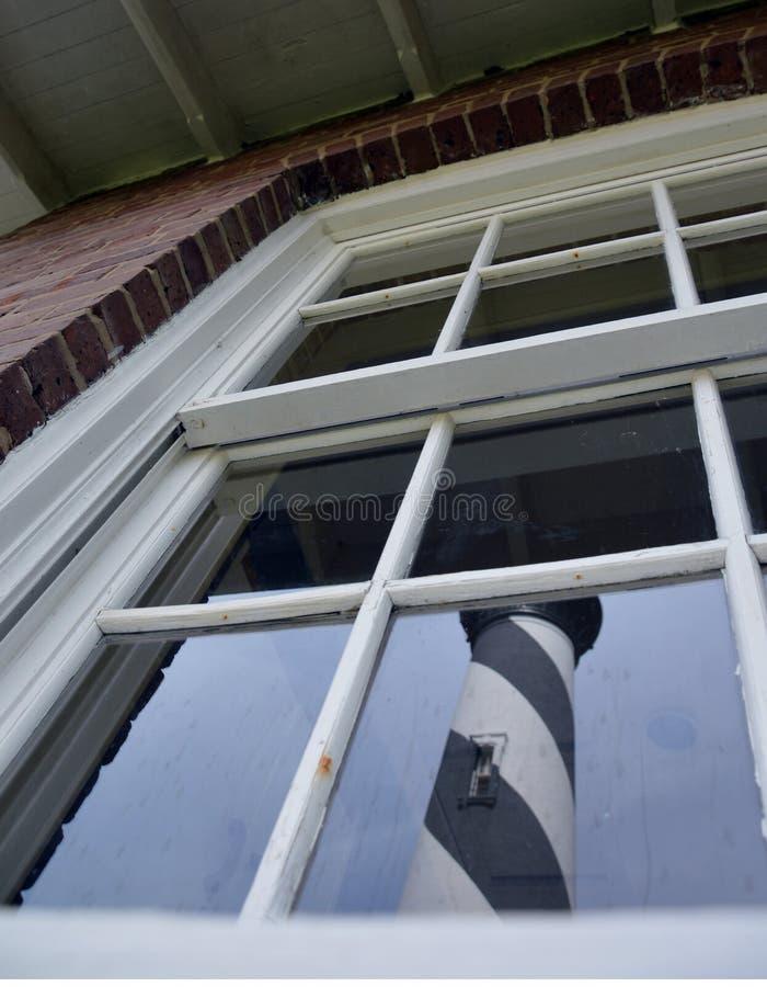 Vuurtorenbezinning in een venster stock afbeeldingen