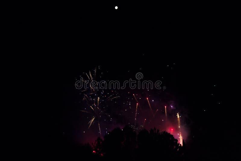 Vuurwerk in een kleurrijke rokerige nevel onder een heldere volle maan royalty-vrije stock foto