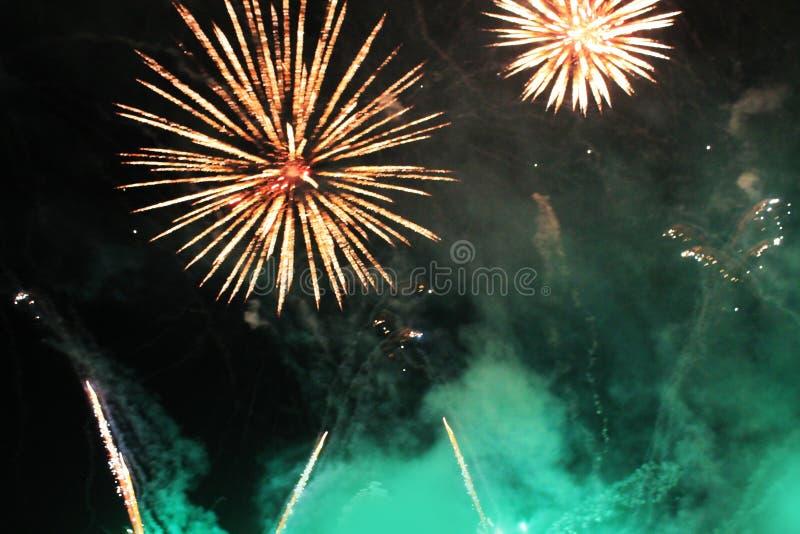 Vuurwerk vuurwerk Hemelse achtergrond Een kleurrijke golf van heldergroene en oranje het flikkeren lichten in de nachthemel tijde royalty-vrije stock fotografie