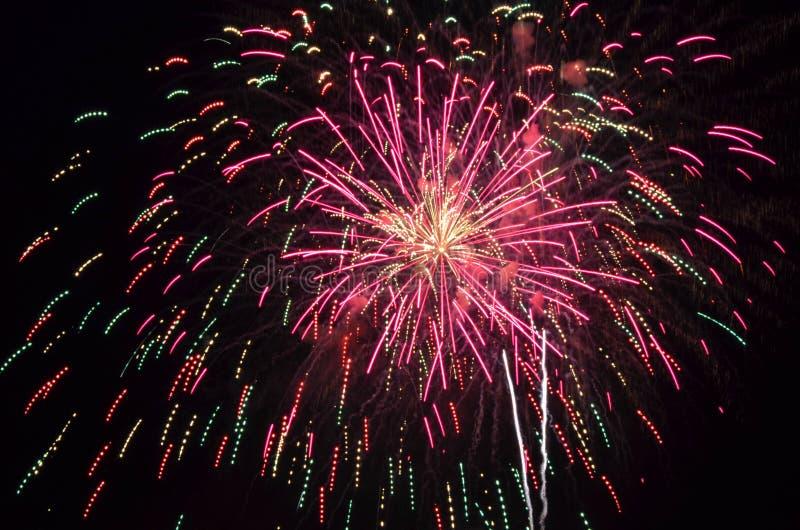 Vuurwerk in kleuren van roze en groen licht omhoog de nachthemel op vier juli stock foto's