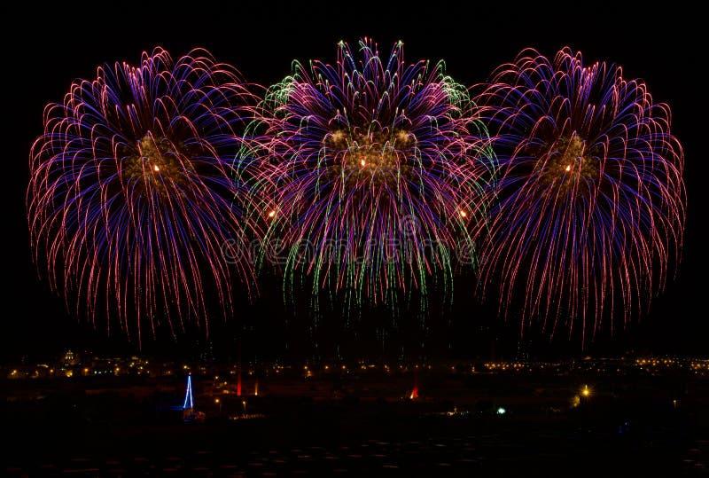 Vuurwerk Kleurrijk verschillend verbazend vuurwerk met de maan, de donkere hemelachtergrond en het huislicht in veel binnen Zurri royalty-vrije stock afbeelding