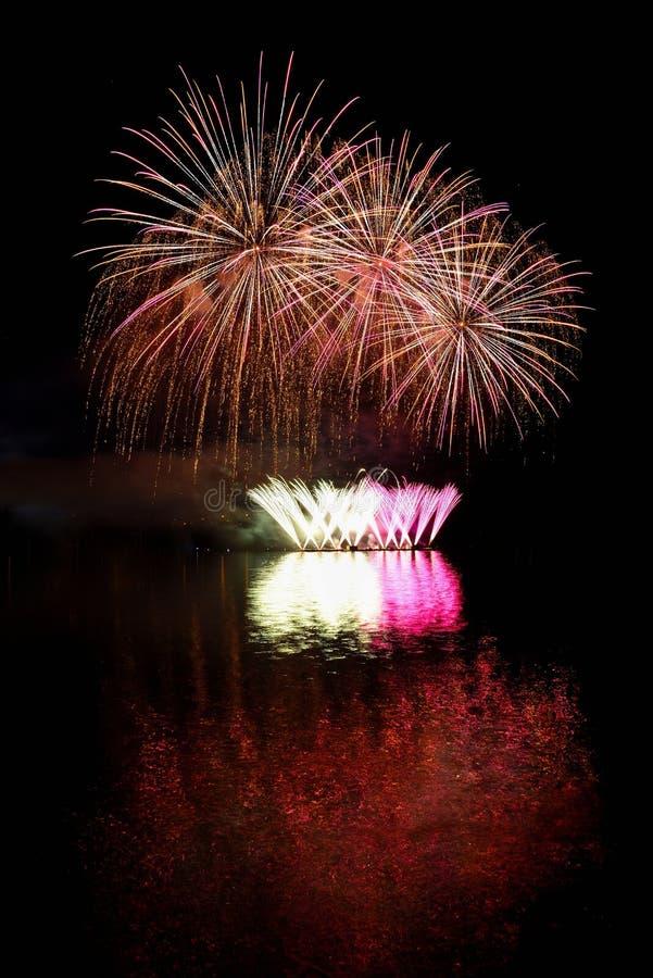 vuurwerk Mooi kleurrijk vuurwerk op de waterspiegel met een schone zwarte achtergrond Pretfestival en wedstrijd van Brandbestrijd stock foto