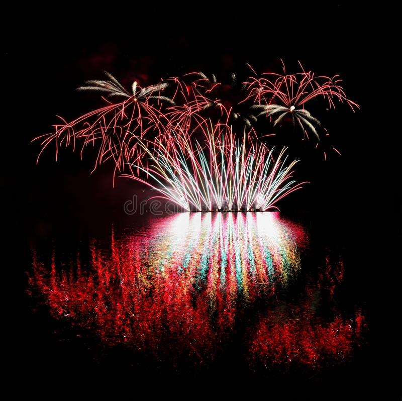 vuurwerk Mooi kleurrijk vuurwerk op de waterspiegel met een schone zwarte achtergrond Pretfestival en wedstrijd van Brandbestrijd royalty-vrije stock foto's