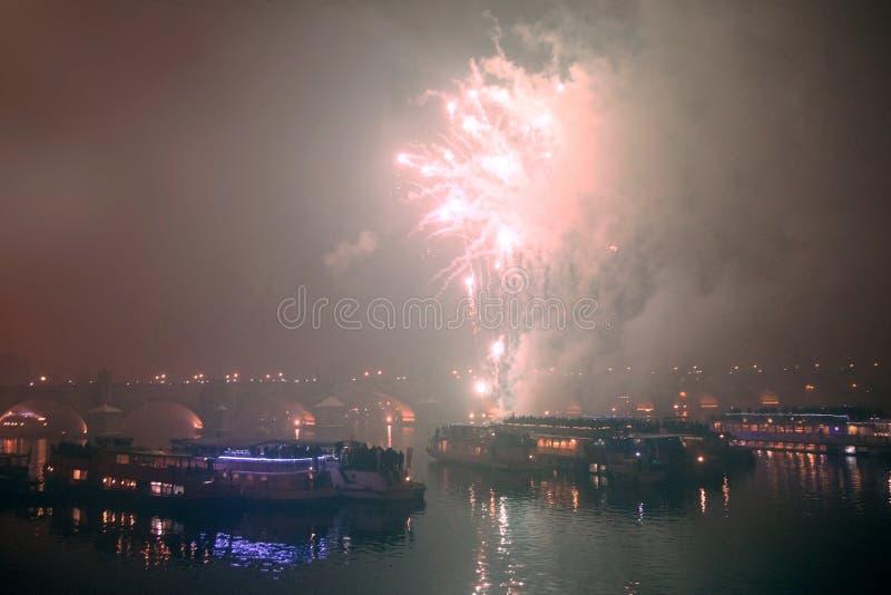 Vuurwerk op Nieuwjaar` s Vooravond over schepen op de Vltava-Rivier in Praag stock fotografie