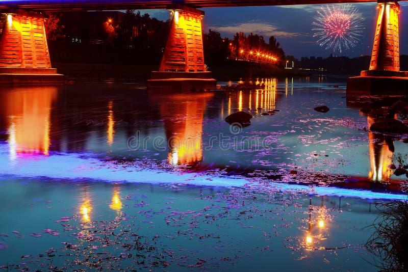 Vuurwerk over de stad van de brugnacht in water Uzhorod wordt weerspiegeld die royalty-vrije stock foto's