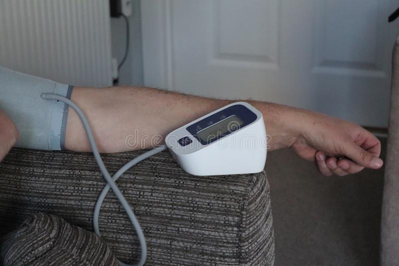 Vuxen arm och blodtryckmaskin i hemmet rekord- läsning för doktorer arkivbild
