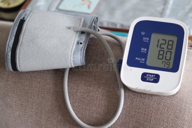 Vuxen arm och blodtryckmaskin i hemmet rekord- läsning för doktorer royaltyfria bilder