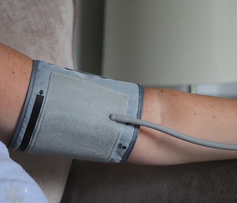 Vuxen arm och blodtryckmaskin i hemmet rekord- läsning för doktorer arkivfoto