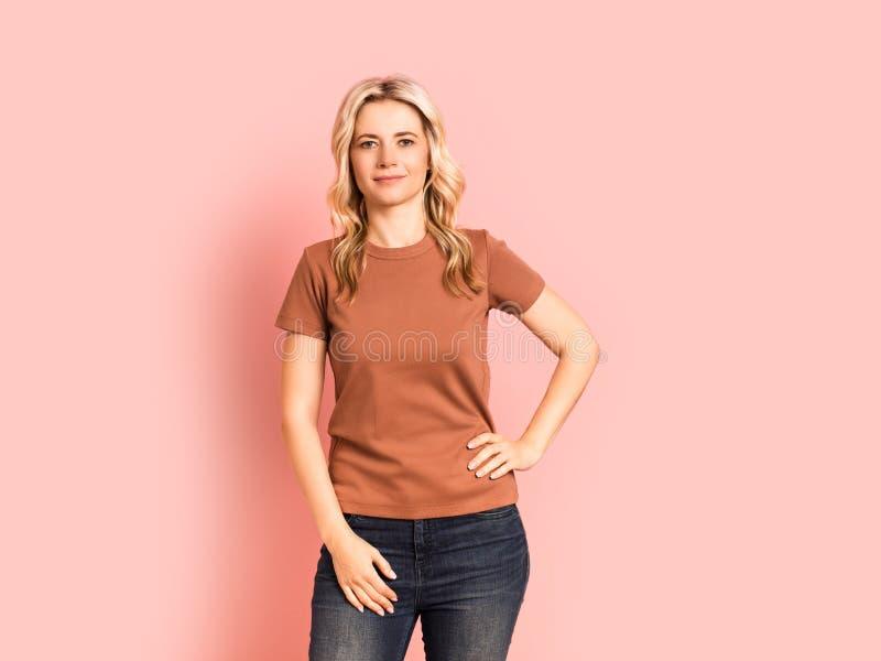 Vuxen attraktiv härlig le stående för blond kvinna, caucasian flicka på rosa bakgrund royaltyfria bilder