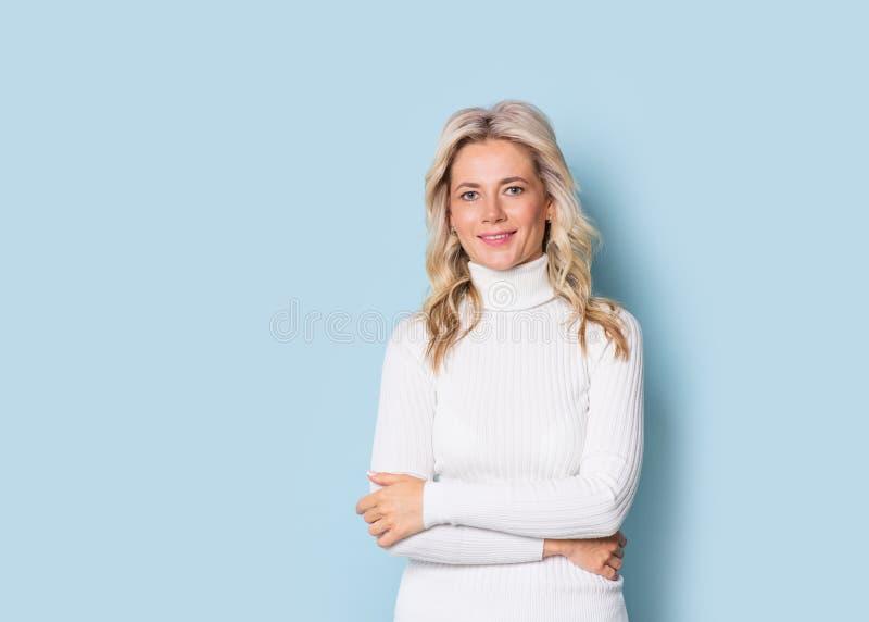 Vuxen attraktiv härlig le stående för blond kvinna en face, cauasian och scandinavian flicka på blå bakgrund fotografering för bildbyråer