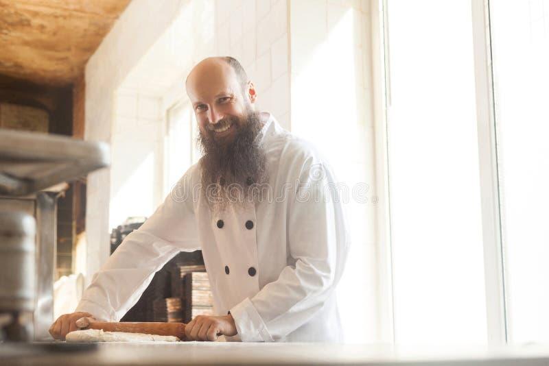 Vuxen bagare med skägget i det vita enhetliga anseendet i arbetsplats och att förbereda bröddegen med kavlen som knådar på degen royaltyfria foton