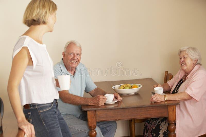 Vuxen dotter som delar kopp te med pensionärföräldrar i kök arkivbilder
