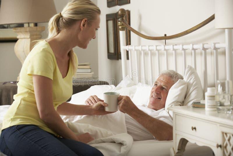 Vuxen dotter som hemma ger hög manlig förälder den varma drinken i säng royaltyfri bild