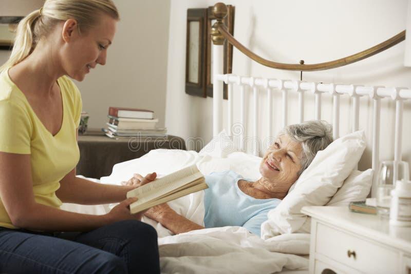 Vuxen dotter som hemma läser till den höga kvinnliga föräldern i säng royaltyfria bilder