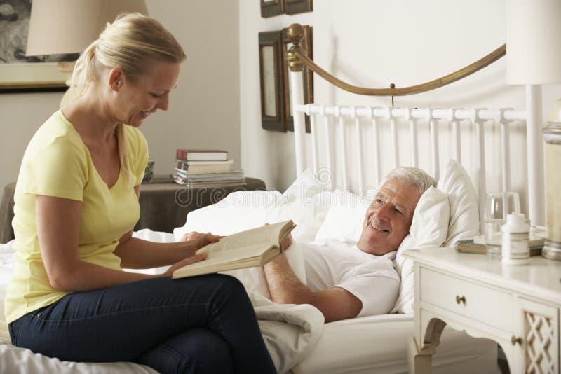 Vuxen dotter som hemma läser till den höga manliga föräldern i säng fotografering för bildbyråer