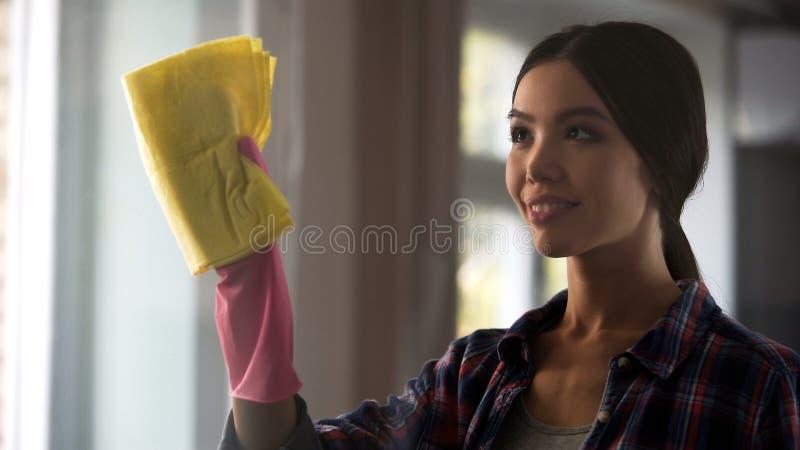 Vuxen dotterportionmoder i allmänhet som gör ren, tvättande fönster, hussysslor royaltyfri foto
