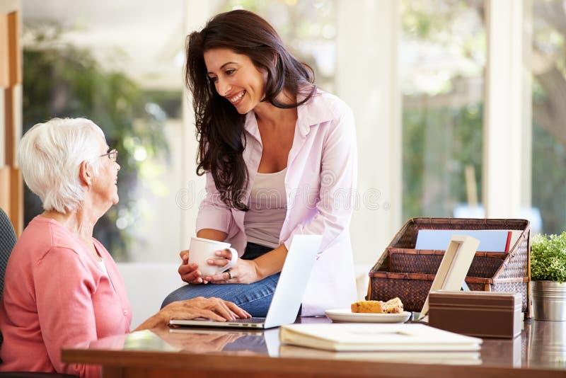 Vuxen dotterportionmoder med bärbara datorn royaltyfria foton
