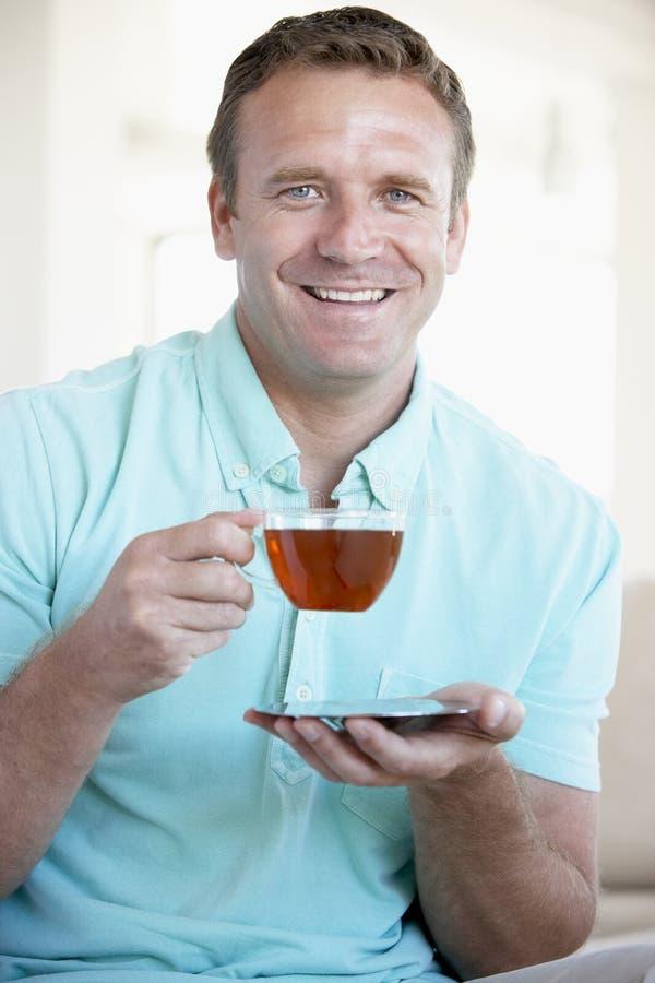 vuxen dricka mitt- tea för man royaltyfri fotografi