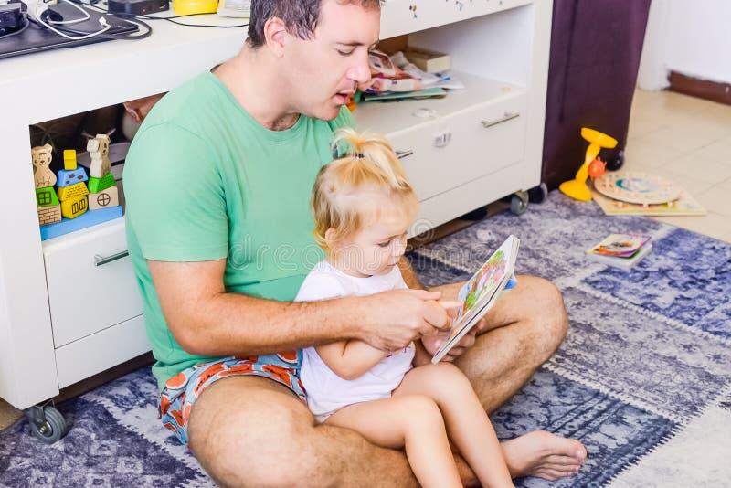 Vuxen fader med lilla barnet som hemma daughtersitting, och läsebokberättelse Liten flickasammanträde på fadervarv Familj barnedu royaltyfri foto