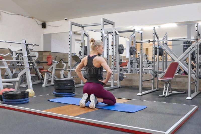 Vuxen härlig kvinnlig blondin som gör sträcka övande yoga i idrottshall arkivbilder