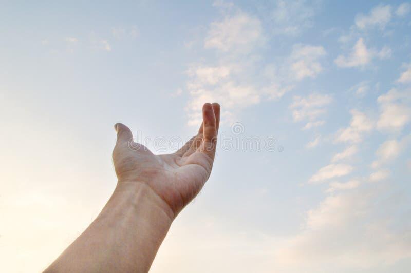 Vuxen hand som ut når in mot himlen arkivfoto