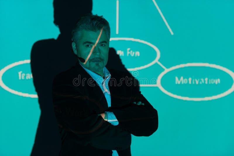 Vuxen instruktör som framme står av skärmen med presentation fotografering för bildbyråer