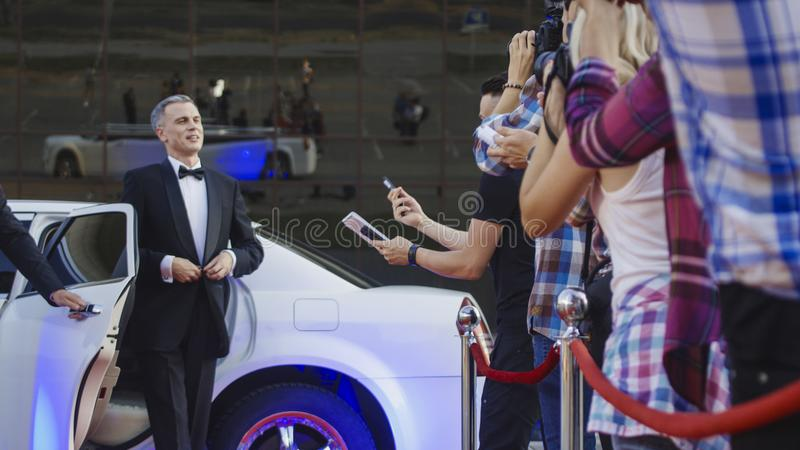 Vuxen kändis som ger autografer på röd matta royaltyfri fotografi