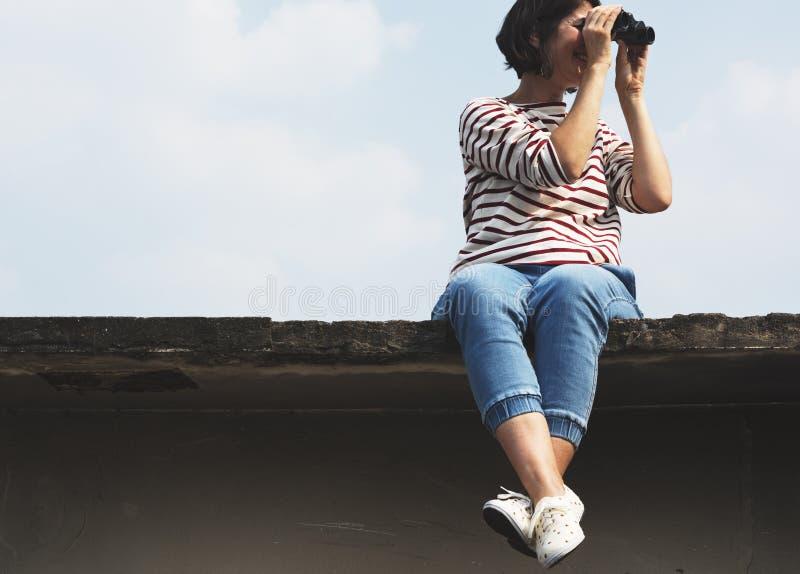 Vuxen kvinna som använder binokulär hållande ögonen på himmel royaltyfria foton