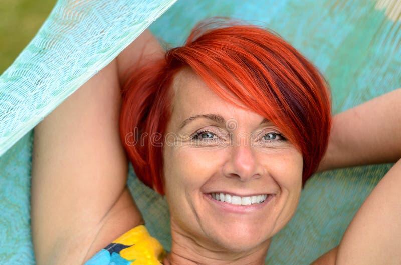 Vuxen kvinna som kopplar av på hängmattan på trädgården arkivbilder