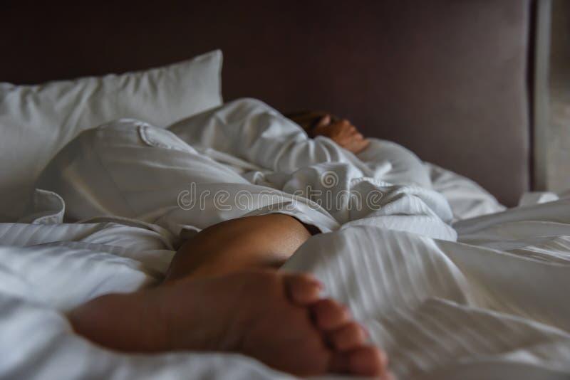 Vuxen kvinna som lägger i säng i framsida för morgonljusbeläggning arkivfoto