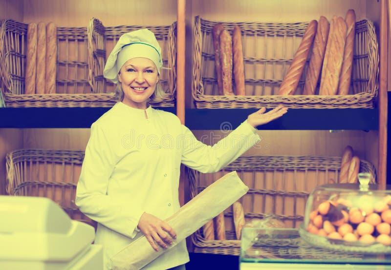 Vuxen kvinna som poserar i bageri med bagetter royaltyfri bild