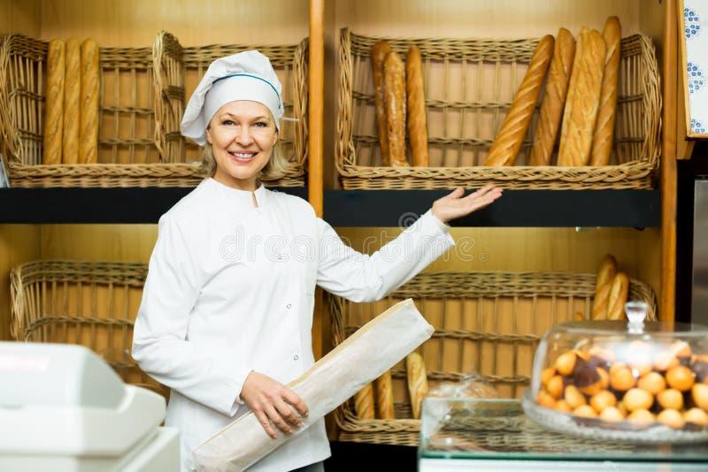 Vuxen kvinna som poserar i bageri med bagetter royaltyfri fotografi
