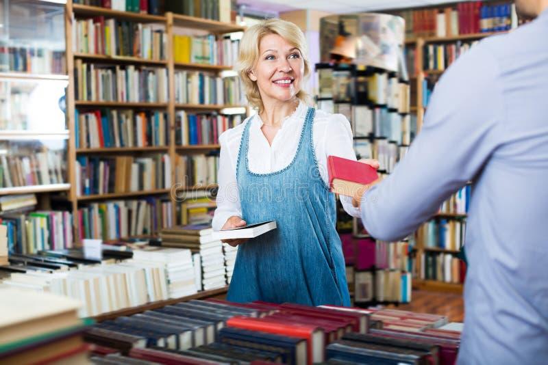 Vuxen kvinna som tar boken och talar till säljaren royaltyfri foto