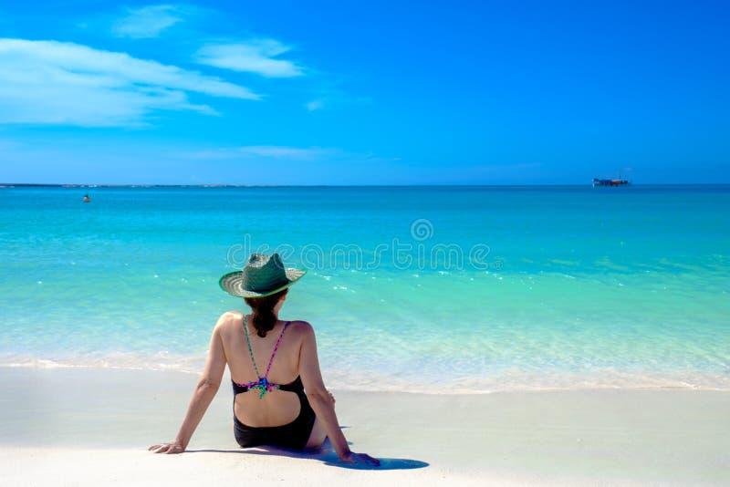 Vuxen kvinna som tar i strandsolen arkivbilder